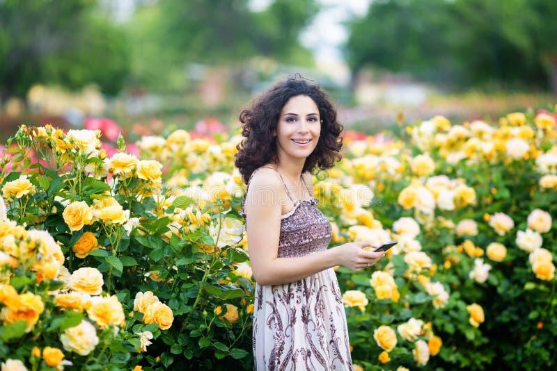 Jonge Kaukasische vrouw met donker krullend haar dichtbij gele roze struik in een roze tuin die aan de camera en de glimlachende  royalty-vrije stock afbeeldingen
