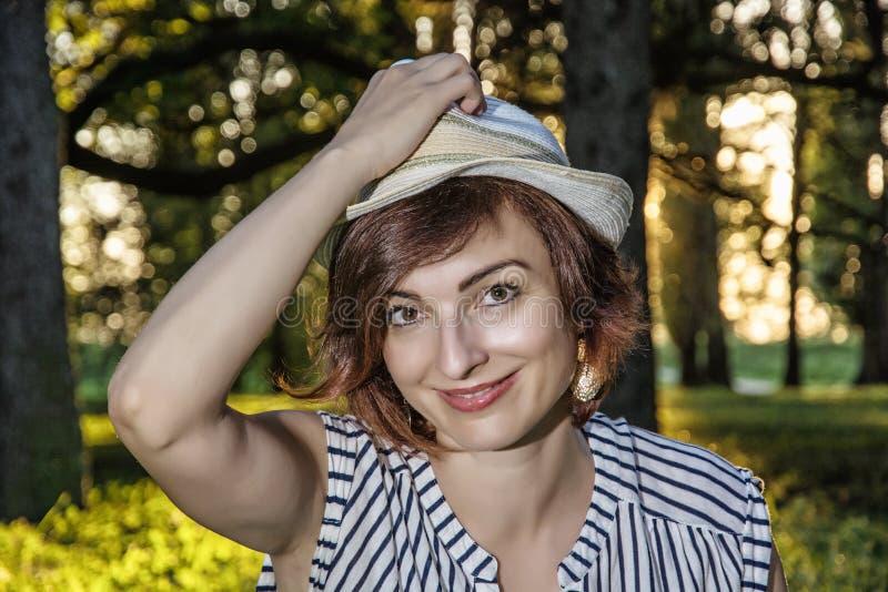 Jonge Kaukasische vrouw met het modieuze sunhat stellen in het bos, royalty-vrije stock foto