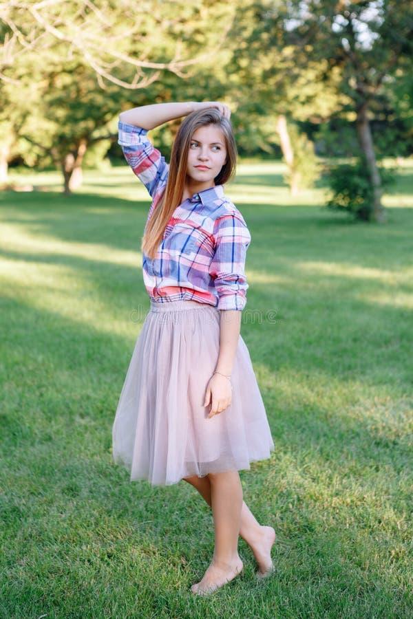 jonge Kaukasische vrouw met lang rood haar in plaidoverhemd het stellen in park royalty-vrije stock foto