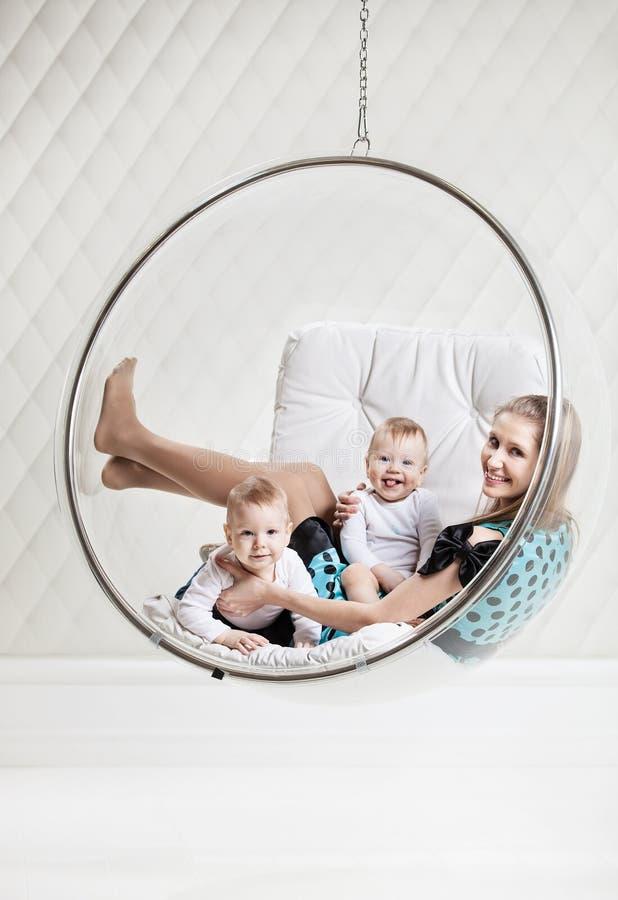 Jonge Kaukasische vrouw met twee babys die pret hebben stock fotografie
