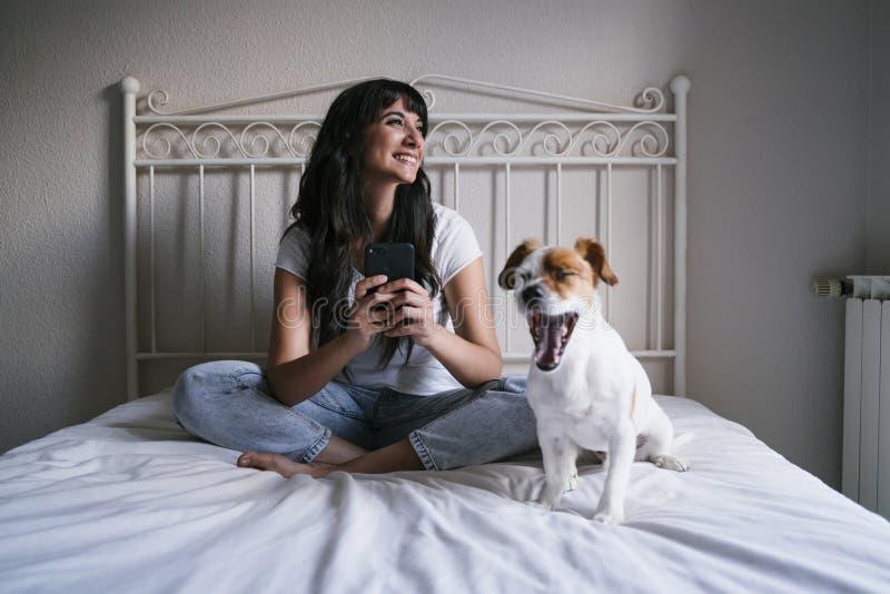 Jonge Kaukasische vrouw op bed die mobiele telefoon met behulp van Leuke kleine hond die bovendien geeuwen Liefde voor dieren en  royalty-vrije stock foto