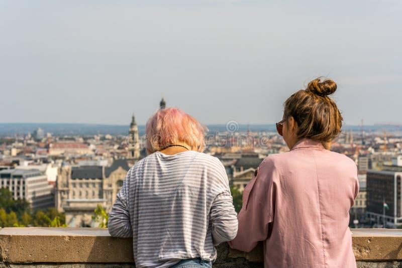 Jonge Kaukasische vrouw twee die over steentraliewerk leunen om de stadsmening van Boedapest Hongarije te ontspannen en te bekijk royalty-vrije stock foto