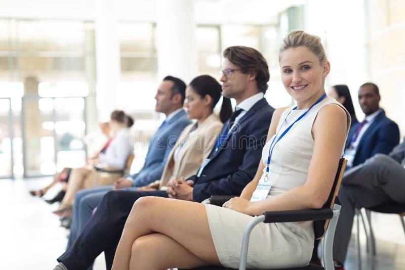Jonge Kaukasische vrouwelijke die stafmedewerker in conferentieruimte wordt gezeten, die aan camera glimlachen stock afbeelding