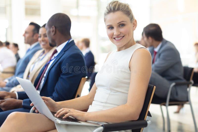 Jonge Kaukasische vrouwelijke uitvoerende gebruikende laptop in conferentieruimte, die aan camera glimlachen stock foto's