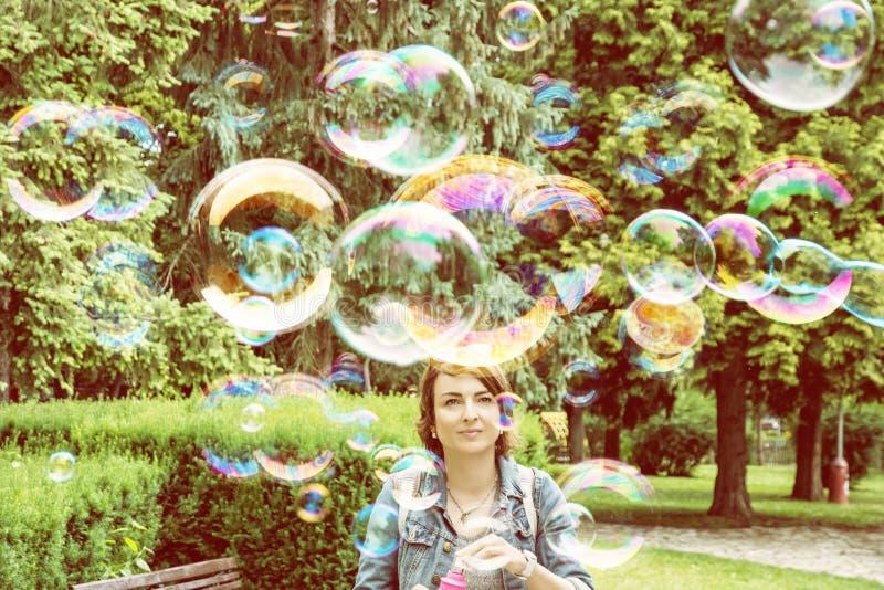 Jonge Kaukasische vrouwen blazende zeepbels in het stadspark stock afbeelding