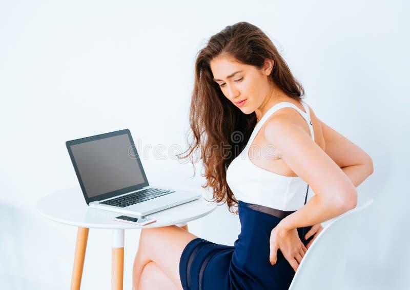 Jonge Kaukasische werkende bedrijfsvrouw op bureau met laptop lijden lager achter en heuppijn als resultaat van bureausyndroom royalty-vrije stock foto's