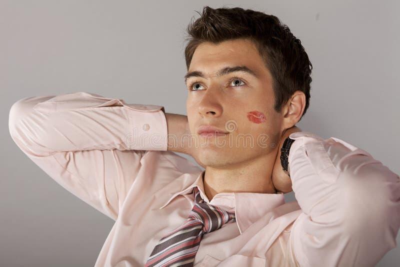 Jonge Kaukasische zakenman met het teken van de lippenstiftkus op zijn wang stock foto's