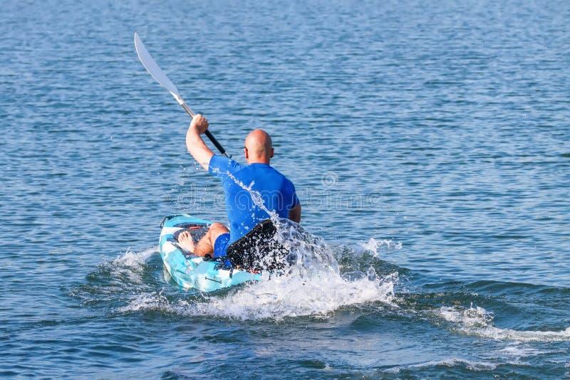Jonge Kayaker-het Paddelen Kajak Sportman die Blauw Water kayaking royalty-vrije stock foto's