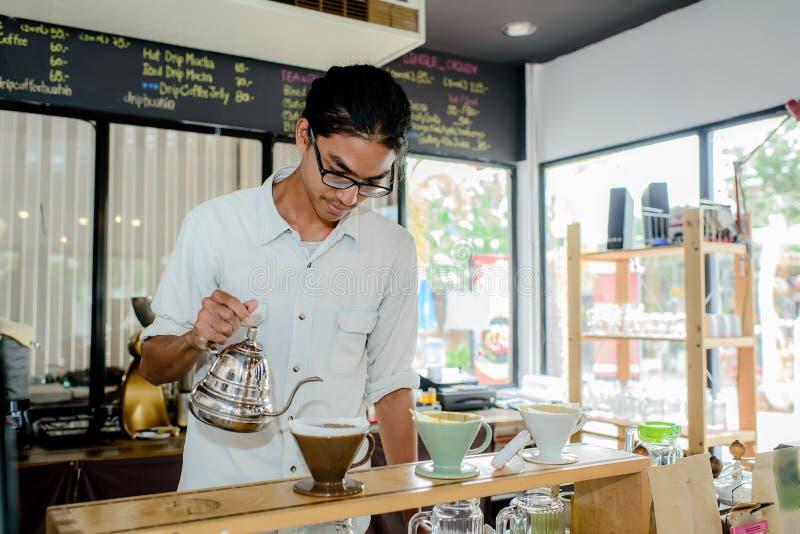 Jonge kelner die kop van koffie maken royalty-vrije stock foto