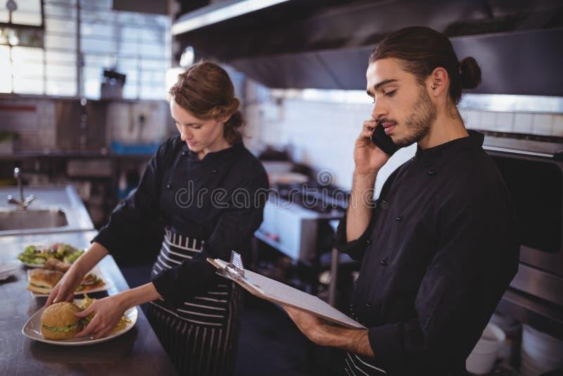 Jonge kelner die op smartphone spreken terwijl serveerster die voedsel in commerciële keuken voorbereiden royalty-vrije stock afbeelding