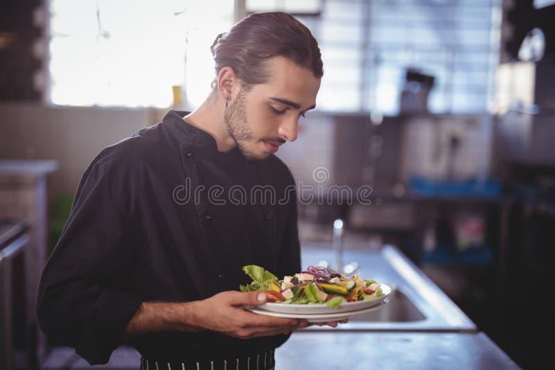 Jonge kelner die verse saladeplaat in commerciële keuken houden stock afbeelding