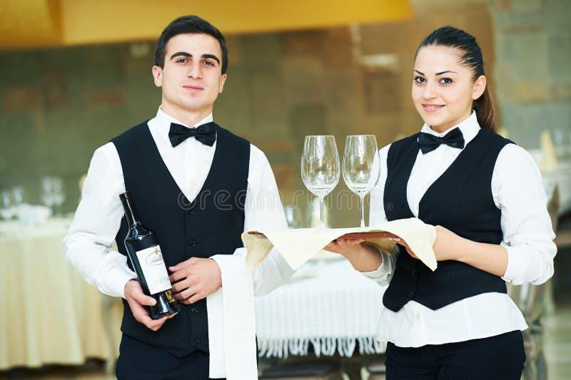 Jonge kelner en serveerster bij de dienst in restaurant stock foto's