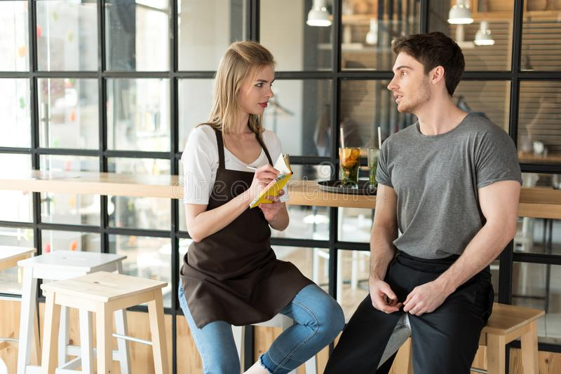 jonge kelner en serveerster die gesprek hebben tijdens onderbreking op het werk stock foto's