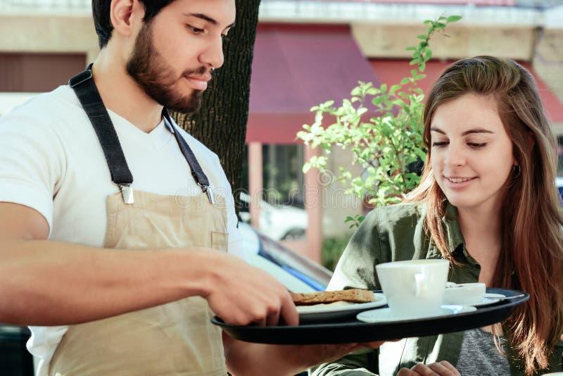 Jonge kelners dienende koffie aan vrouwelijke klant royalty-vrije stock afbeeldingen