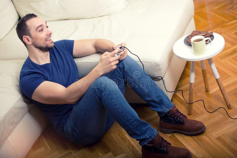 Jonge kerel die computer van spel genieten, die met bedieningshendel spelen stock foto