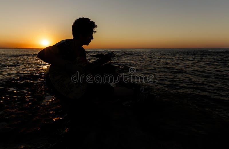 Jonge kerel die een gitaar spelen bij zonsondergang stock foto's