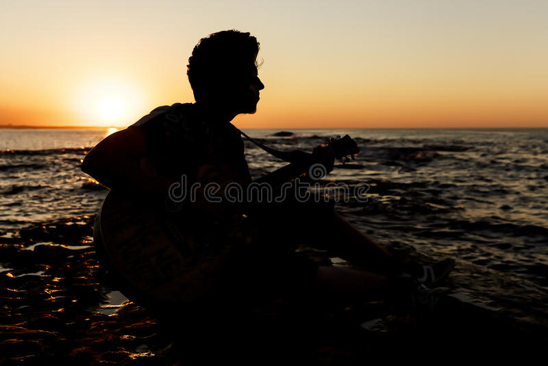 Jonge kerel die een gitaar spelen bij zonsondergang stock fotografie