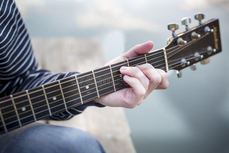 Jonge kerel die een gitaar spelen bij zonsondergang op rivier Sluit omhoog zijn handen en gitaarhals stock foto's