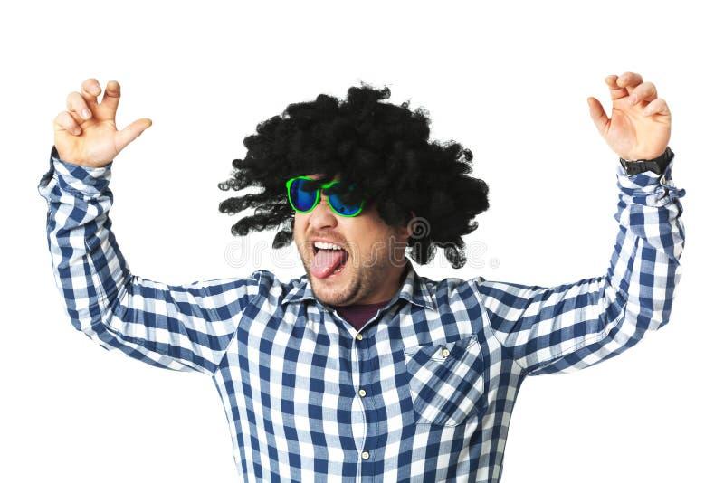 Jonge kerel die pret in zwarte die pruik hebben - op wit wordt geïsoleerd stock afbeelding