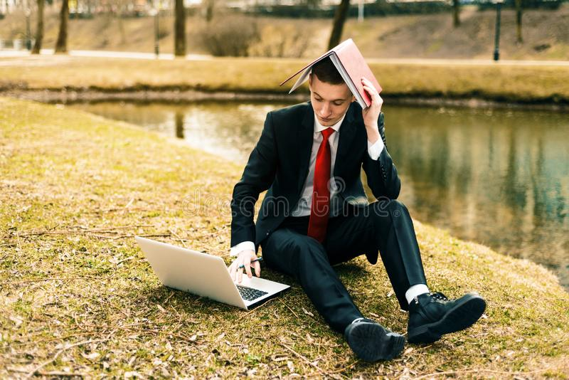 Jonge kerel die van het werk wordt vermoeid mens in een kostuum die op de aard dichtbij het meer lopen royalty-vrije stock afbeeldingen