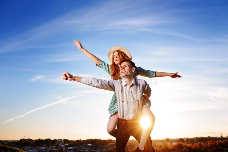 Jonge kerel die vrolijk meisje zoals vliegtuig op de achtergrond van hemel vervoeren per kangoeroewagen royalty-vrije stock fotografie