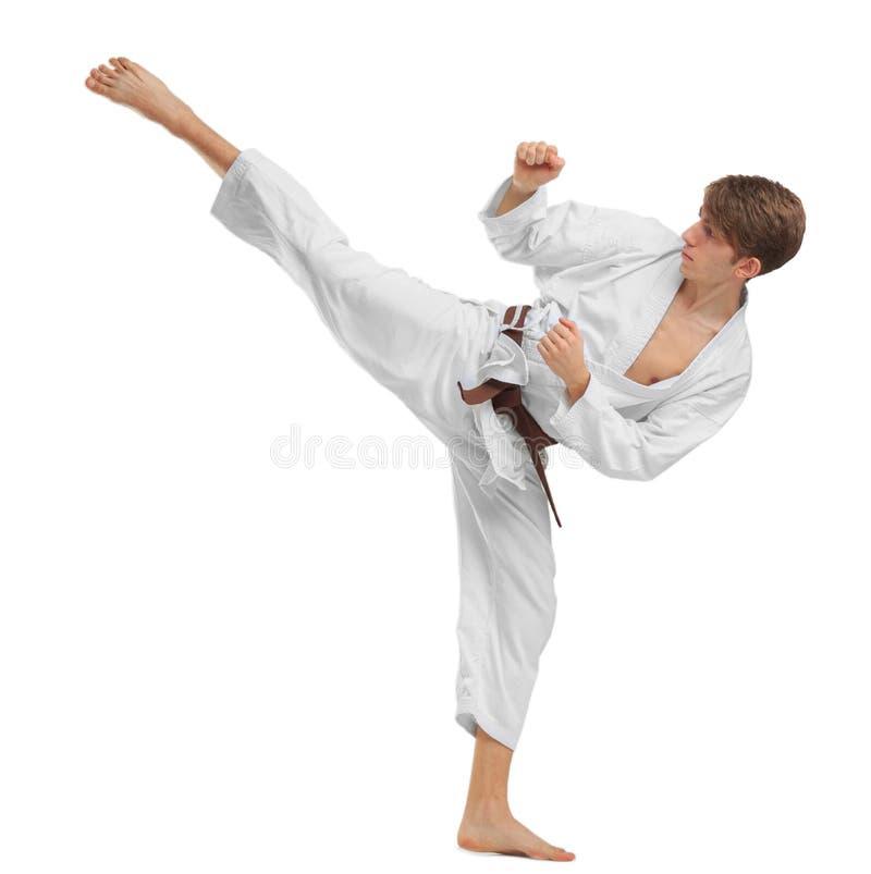 Jonge kerel karatek met bruine riem op wit geïsoleerde achtergrond royalty-vrije stock afbeeldingen