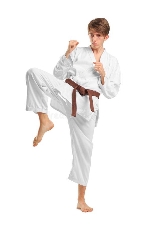 Jonge kerel karatek met bruine riem op wit geïsoleerde achtergrond stock afbeeldingen