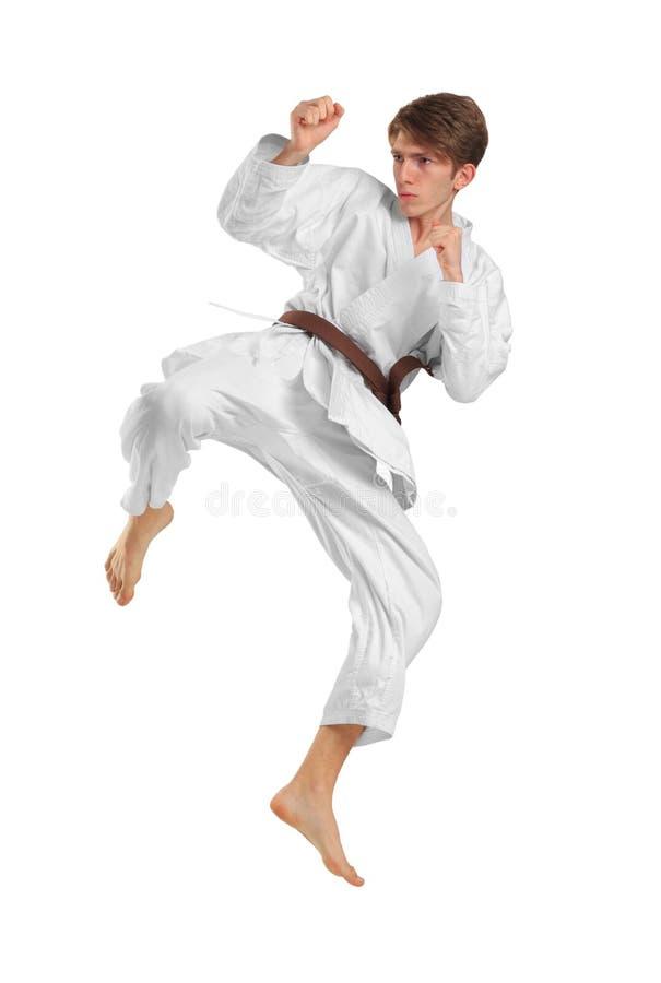 Jonge kerel karatek met bruine riem op wit geïsoleerde achtergrond royalty-vrije stock afbeelding