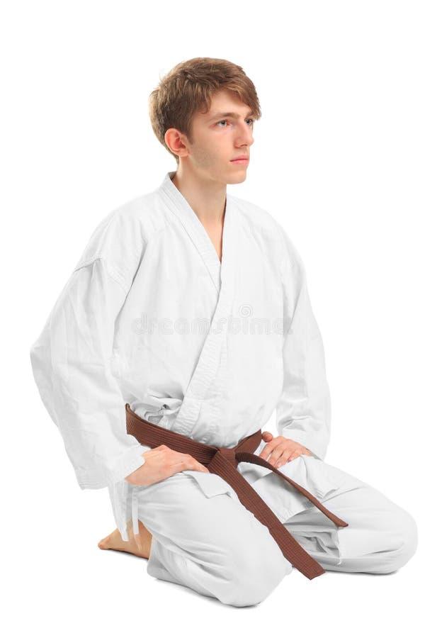 Jonge kerel karatek met bruine riem op wit geïsoleerde achtergrond stock fotografie