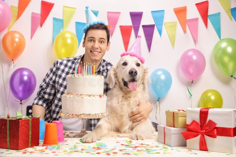 Jonge kerel met een hond die een verjaardag vieren stock afbeelding