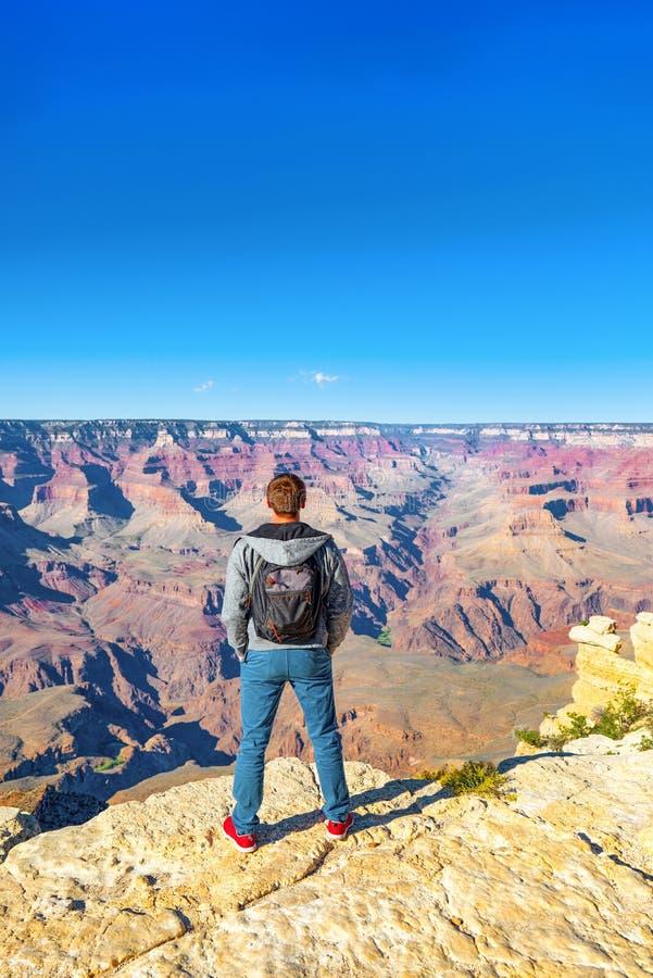 Jonge kerel op de rand van een klip op Grand Canyon stock foto's