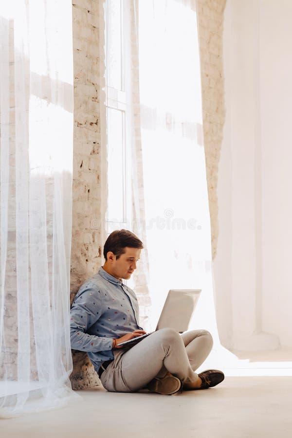 Jonge kerel op de vloer die aan laptop in licht zonnig binnenland werken, freelancer, notitieboekje stock foto's