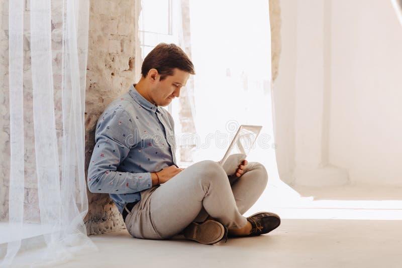 Jonge kerel op de vloer die aan laptop in licht zonnig binnenland werken, freelancer, notitieboekje royalty-vrije stock fotografie