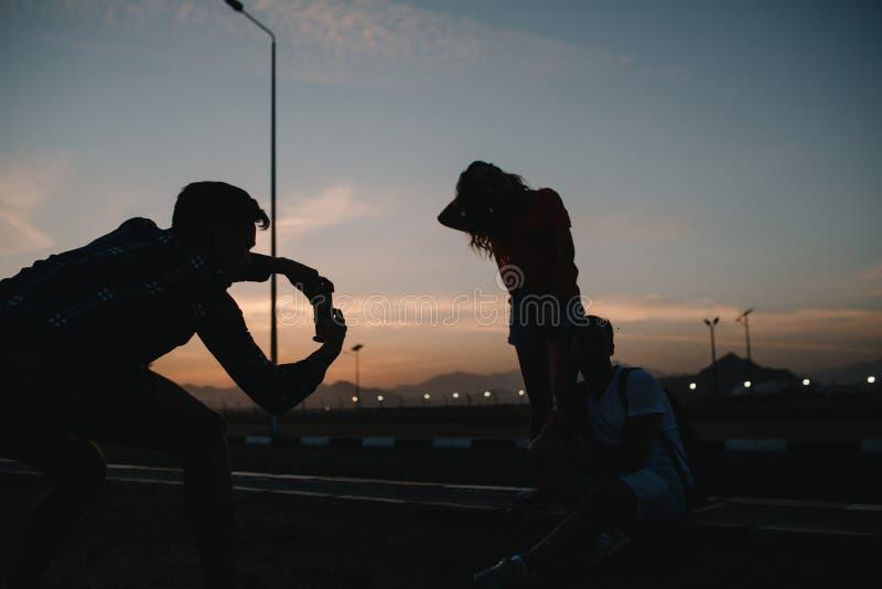 Jonge kerel van rug die foto op telefoon van paar op weg op zonsondergangachtergrond nemen Het reizen in tropisch land stock fotografie