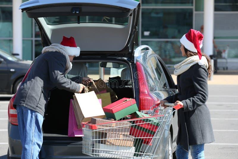 Jonge Kerstmisaankopen van de paarlading in autoboomstam op winkelcomplexparkeren stock foto's