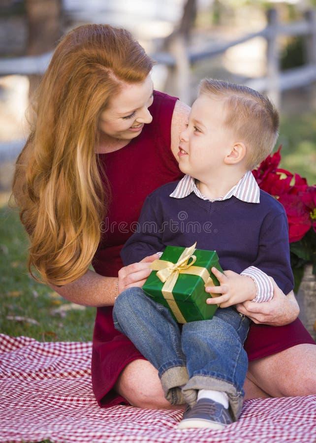 Jonge Kerstmisgift van de Jongensholding met Zijn Mamma in Park stock afbeelding