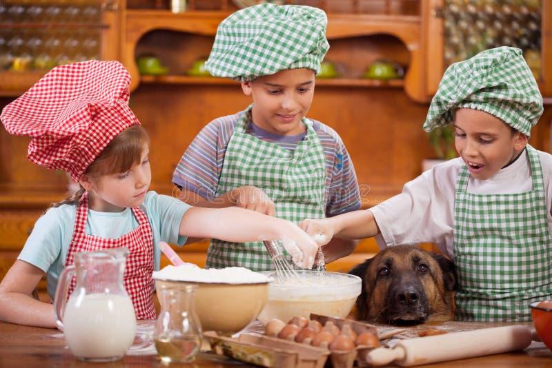 Jonge kinderen die koekjes in de keuken, Duitse herder voorbereiden royalty-vrije stock foto