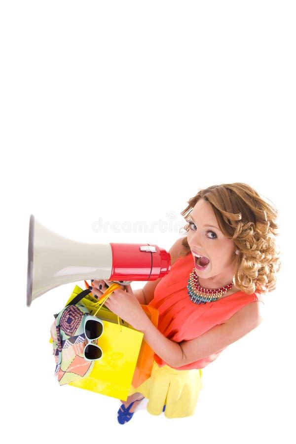 Jonge kleurrijke geklede vrouw die en het schreeuwen trogluidspreker winkelen royalty-vrije stock fotografie
