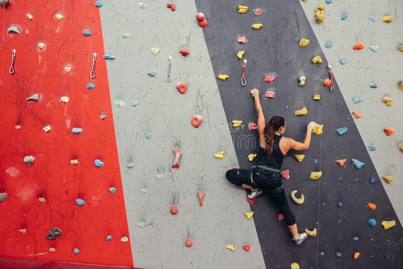 Jonge klimmervrouw die op praktische rots in het beklimmen van centrum, het bouldering beklimmen royalty-vrije stock afbeeldingen