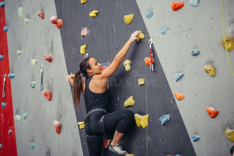 Jonge klimmervrouw die op praktische rots in het beklimmen van centrum, het bouldering beklimmen stock afbeeldingen