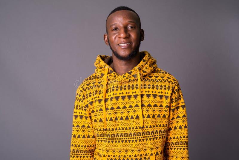 Jonge knappe Afrikaanse mens met kort haar tegen grijze backgrou stock fotografie