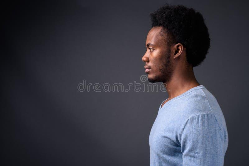 Jonge knappe Afrikaanse mens tegen grijze achtergrond royalty-vrije stock afbeeldingen
