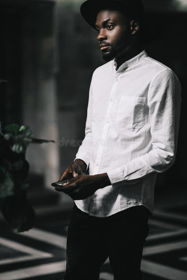 Jonge knappe afro Amerikaanse jongen in modieuze hipsterhoed stock fotografie