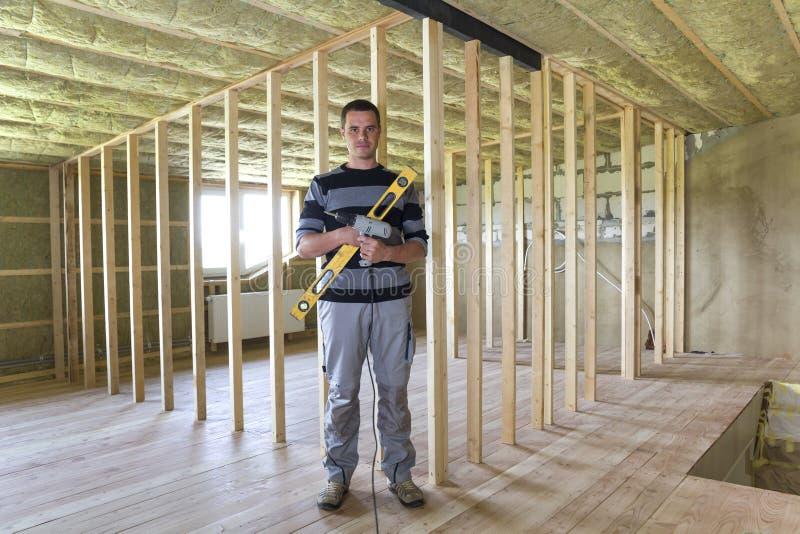 Jonge knappe arbeider met niveau en schroevedraaier die in camera in grote lichte zolderruimte met eiken vloer, geïsoleerd plafon royalty-vrije stock foto