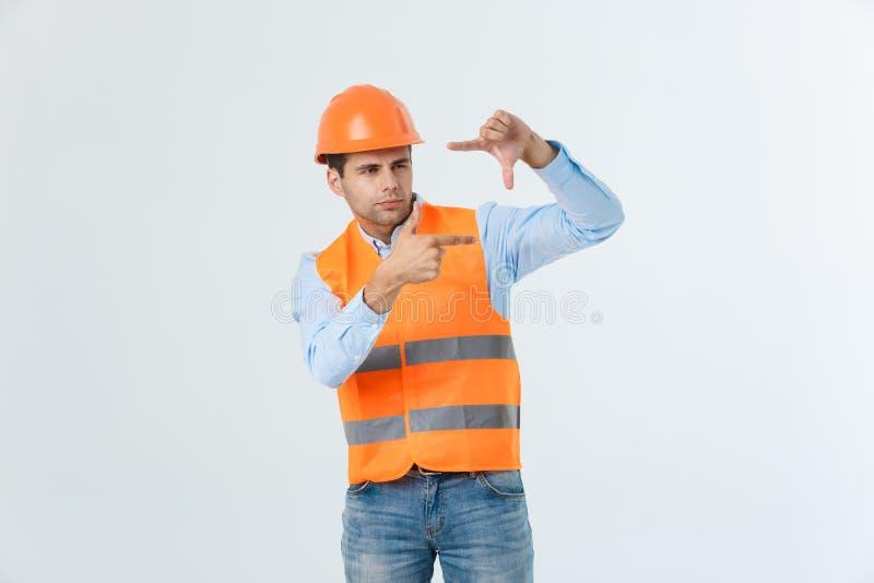Jonge knappe architecmens met het dragen van veiligheidshelm over geïsoleerde achtergrond die kader met handen en vingers maken m royalty-vrije stock afbeelding