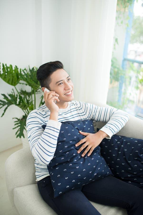 Jonge knappe Aziatische mens die moderne mobiele slimme telefoonzitting gebruiken royalty-vrije stock foto's