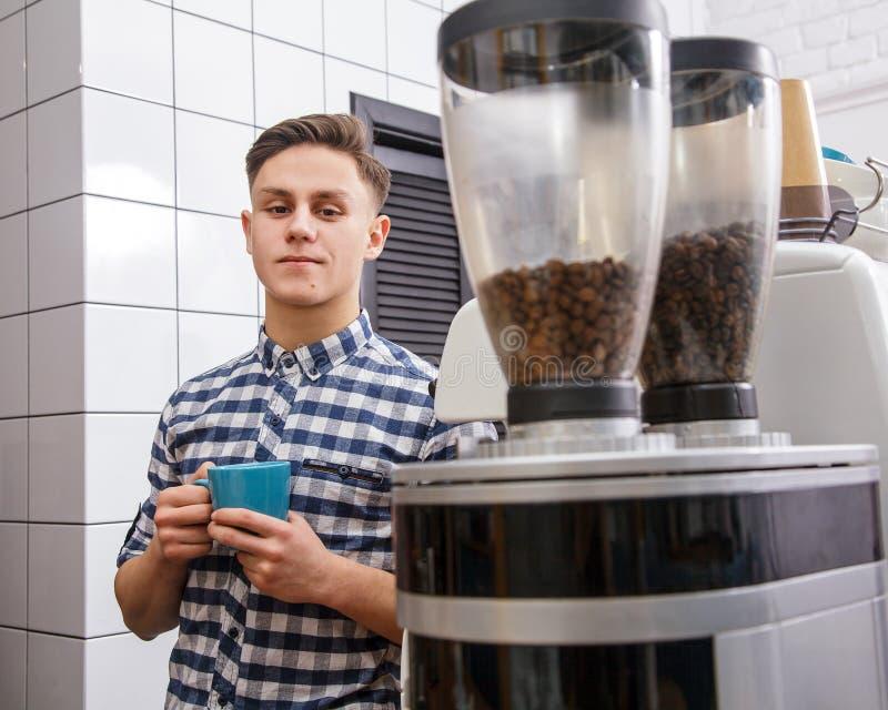 Jonge knappe barista die hipster tot de korrels maken van de de mensenmachine van de koffiekoffie hete stoom de cappuccinodrank v royalty-vrije stock foto's
