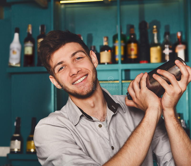 Jonge knappe barman in bar die en alcoholcocktail schudden mengen stock foto