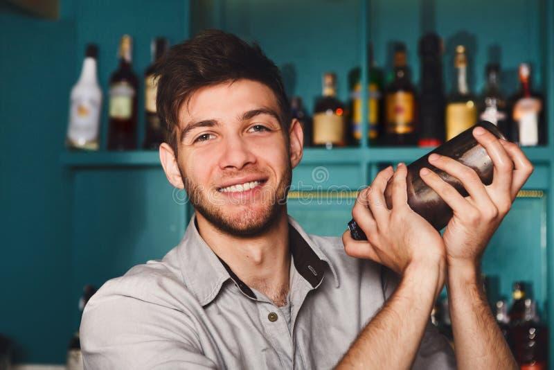 Jonge knappe barman in bar die en alcoholcocktail schudden mengen royalty-vrije stock foto's