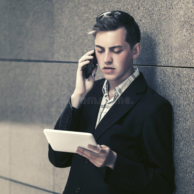 Jonge knappe bedrijfsmens gebruikend tabletcomputer en uitnodigend celtelefoon stock afbeelding